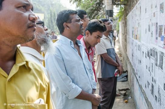 Die Leute informieren sich durch die an Wänden ausgehängten Zeitungen über das aktuelle Geschehen.