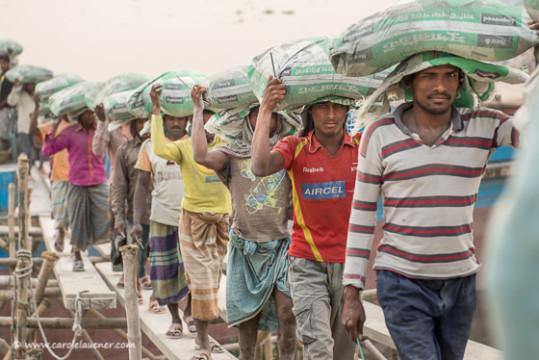 ...während die Eltern daneben für zwei bis drei Franken pro Tag Sand und Steine von einem Boot an Land tragen.