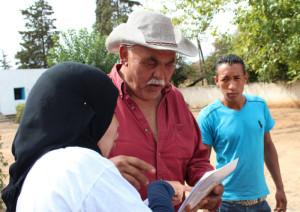 Une activiste de Lam Echaml détaille à un villageois la procédure pour participer aux élections.