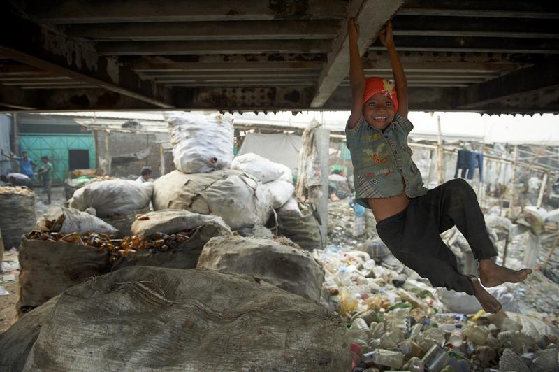Ein Kind der Fabrikarbeiter spielt unter der Brücke