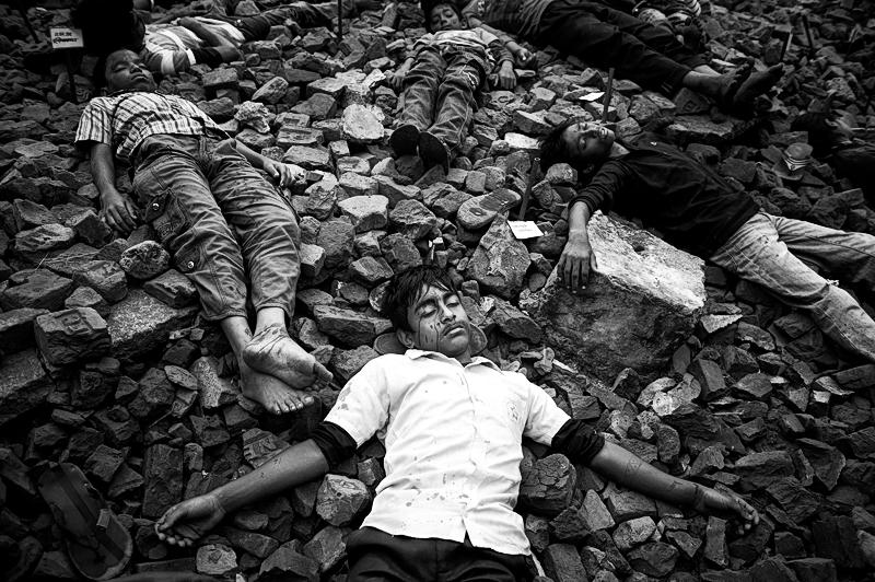 Schüler stellen die Opfer des Martyred Intellectuals Day nach