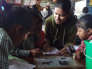 Lehrerin Prerana Adhikari hilft ihren Schülern bei den Aufgaben.