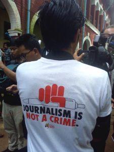 """Journalism is not a crime"" steht auf dem Tshirt dieses Reporters"