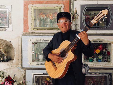 Mann mit Gitarre vor Gräbern.