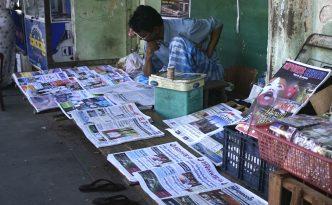 Lesender Zeitungsverkäufer in Myanmar